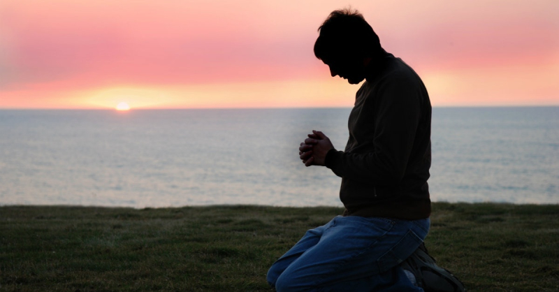 12062-man-kneeling-praying-sunrise-ocean-horizon-hands-together-clasped-head-bowed.1200w.tn